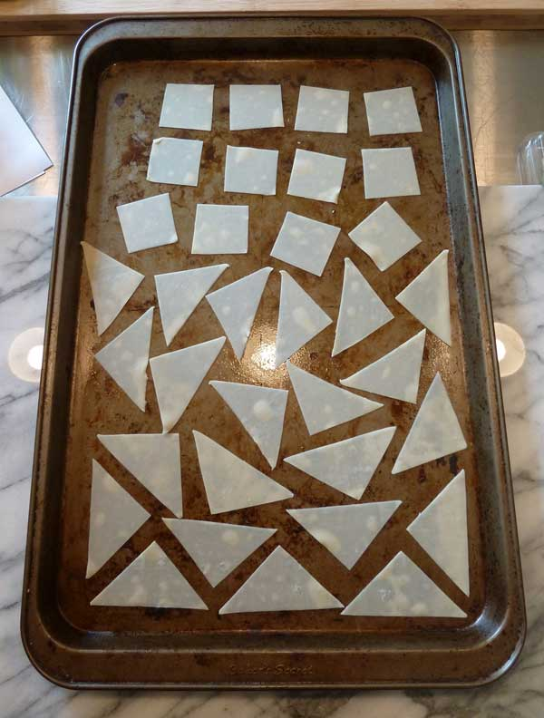 Place the sliced wonton wrappers on a nonstick baking sheet.