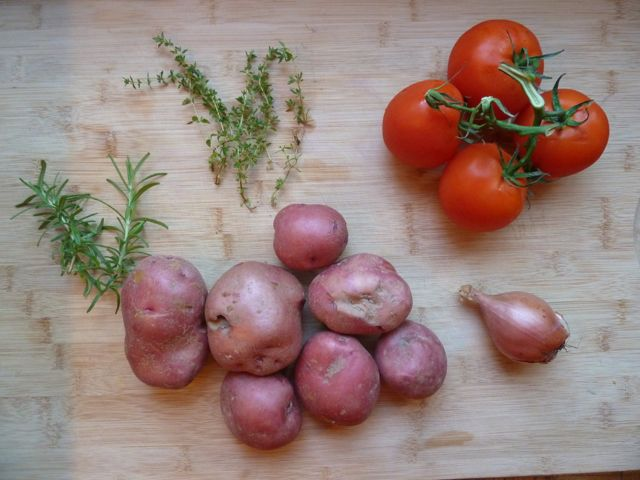 Fresh thyme, rosemary, tomatoes, potatoes and one shallot.