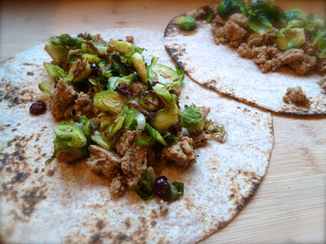 Healthy Turkey Burrito topped with brussel sprouts, leeks and cranberries.