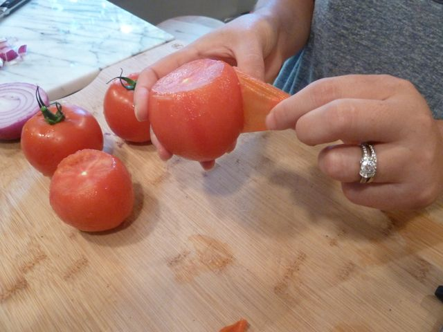 Blanch, then peel the skin off the tomatoes.