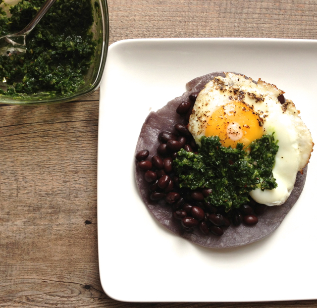 Herb salsa served with beans and egg on a crispy blue corn tortilla.